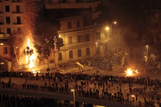 Pro-government demonstrators, bottom, clash with anti-government demonstrators, top right, as a palm tree burns from a firebomb, in Tahrir Square, the center of anti-government demonstrations, in Cairo, Egypt, early Thursday, Feb. 3, 2011. Thousands of supporters and opponents of Egyptian President Hosni Mubarak battled in Cairo's main square all day Wednesday, raining stones, bottles and firebombs on each other in scenes of uncontrolled violence as soldiers stood by without intervening. Government backers galloped in on horses and camels, only to be dragged to the ground and beaten bloody. (AP Photo/Lefteris Pitarakis)